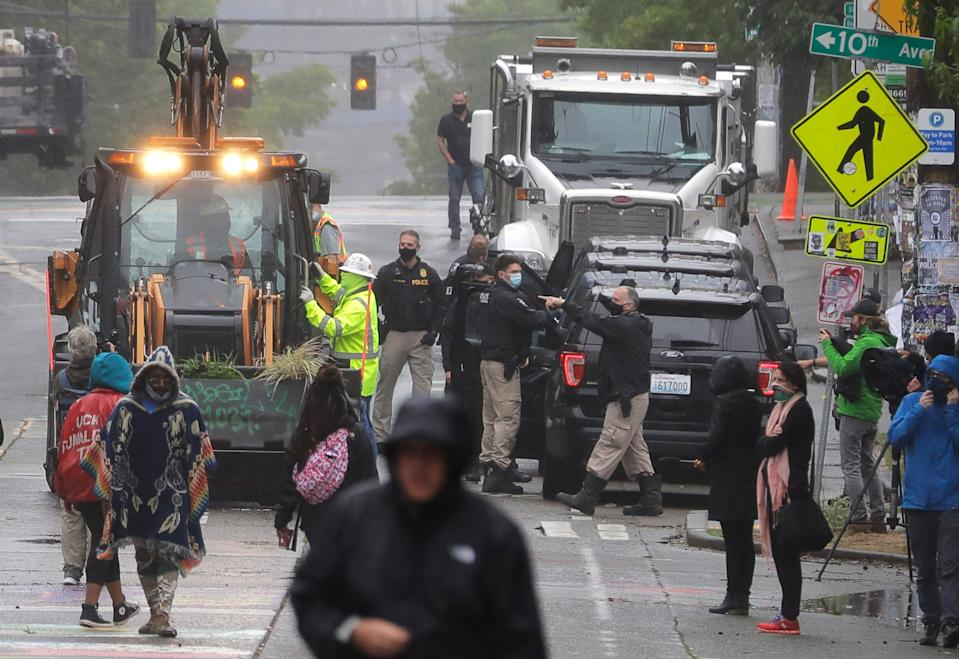 Seattle Police look on as Department of Transportation workers remove barricades at the intersection of 10th Ave. and Pine St., Tuesday, June 30, 2020