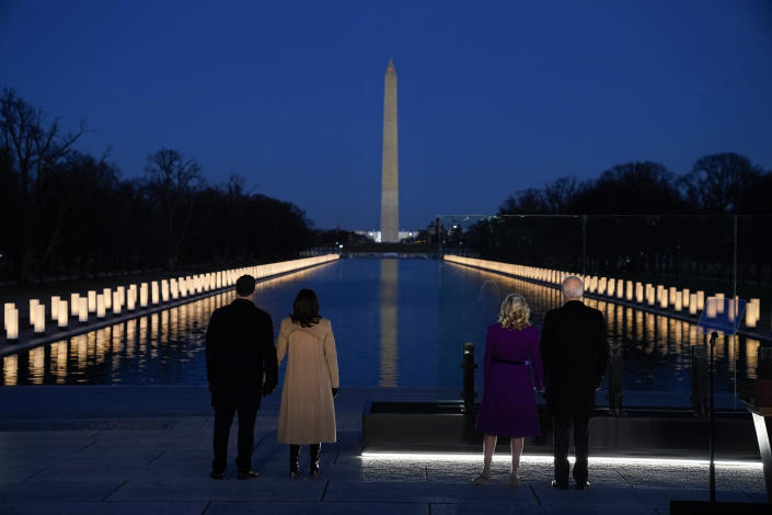 "With the Washington Monument in the background, President-elect Joe Biden with his wife Jill Biden and Vice President-elect Kamala Harris with her husband Doug Emhoff listen as Yolanda Adams sings ""Hallelujah"" during a COVID-19 memorial, with lights placed around the Lincoln Memorial Reflecting Pool, Tuesday, Jan. 19, 2021, in Washington. (AP Photo/Evan Vucci)"