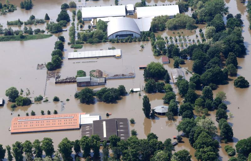 In this aerial view the Magdeburg, Germany,   sports park is flooded by river Elbe, Sunday June 9, 2013,. Thousands of people have been evacuated from their homes in a region of eastern Germany where the Elbe river has flooded and burst through a dam, officials said Sunday. More than 20  people have been killed by a week of flooding in central Europe, as rivers such as the Danube, the Elbe and the Vlatava have overflowed after heavy rains and caused extensive damage in central and southern Germany, the Czech Republic, Austria, Slovakia and Hungary. (AP Photo/dpa, Jens Wolf(