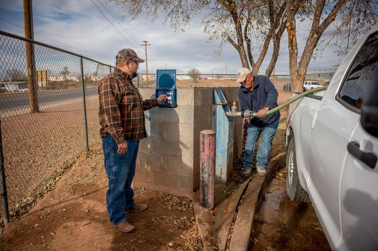 Leroy Canyon and Brandon Canyon are pictured getting getting water from the water tanks in Tuba City.(Photograph by Mary F. Calvert)