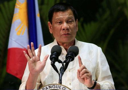 Philippine President Duterte gestures while answering questions during a news conference upon arrival from a trip to Myanmar and Thailand at an international airport in Manila