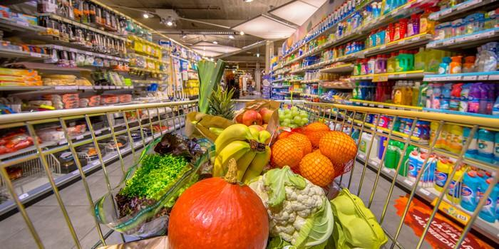 A cart filled with produce in a grocery aisle.
