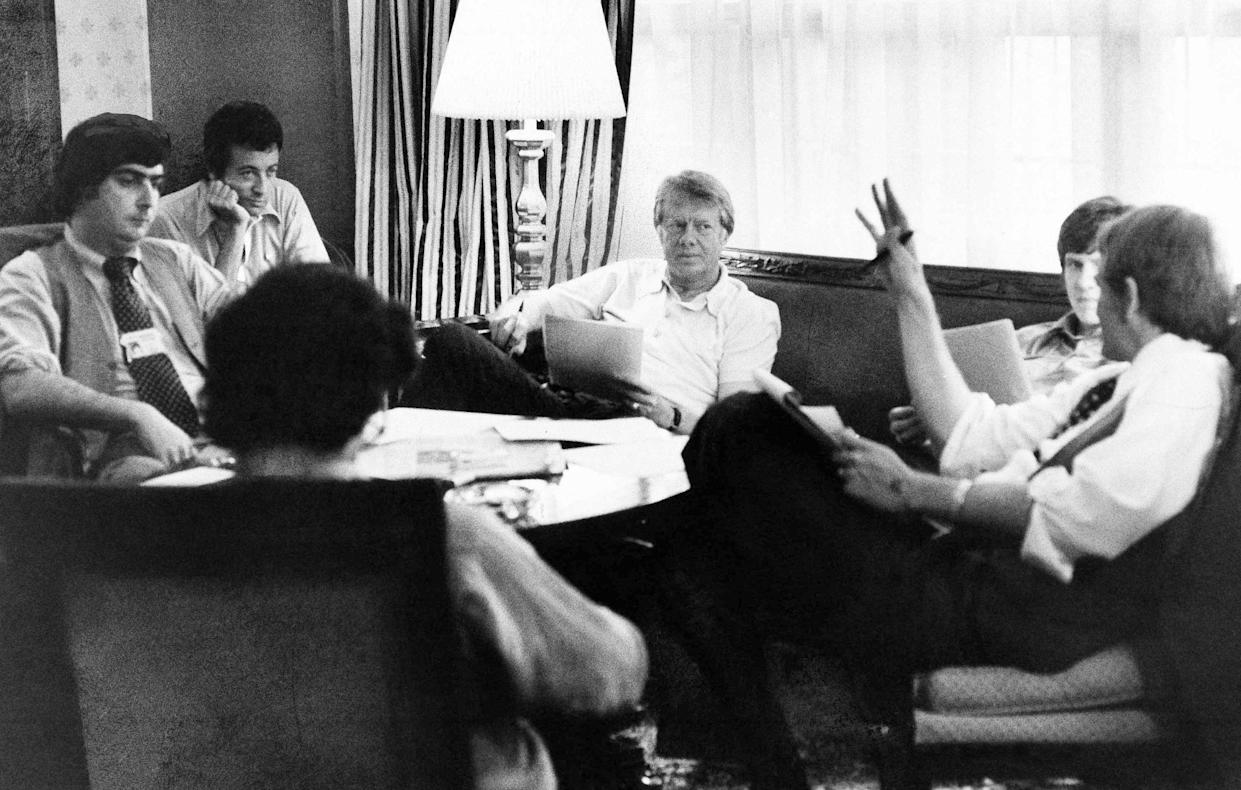 Jimmy Carter meets with his staff in New York, July 14, 1976. From left, facing camera: Pat Caddell, Jerry Rafshoon, Carter, his son, Chip, and Jody Powell. With back to camera is Pat Anderson. (Photo: AP)