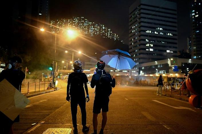 """The protesters staged a second night of """"hit-and-run"""" rallies, splitting into small groups that scattered across the city to set up temporary roadblocks and face off against riot police (AFP Photo/Manan VATSYAYANA)"""