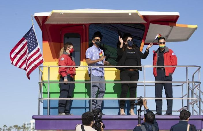 LONG BEACH, CA - JUNE 10: Long Beach Mayor Robert Garcia and Councilwoman Cindy Allen, flanked by lifeguards Devon Bebee, left, and Jeremy Rocha, celebrate the unveiling of a new rainbow-colored lifeguard tower at Long Beach to replace the one that burned down in March. The tower serves as a symbol of LGBTQ+ pride. Photographed on Thursday, June 10, 2021 in Long Beach, CA. (Myung J. Chun / Los Angeles Times)