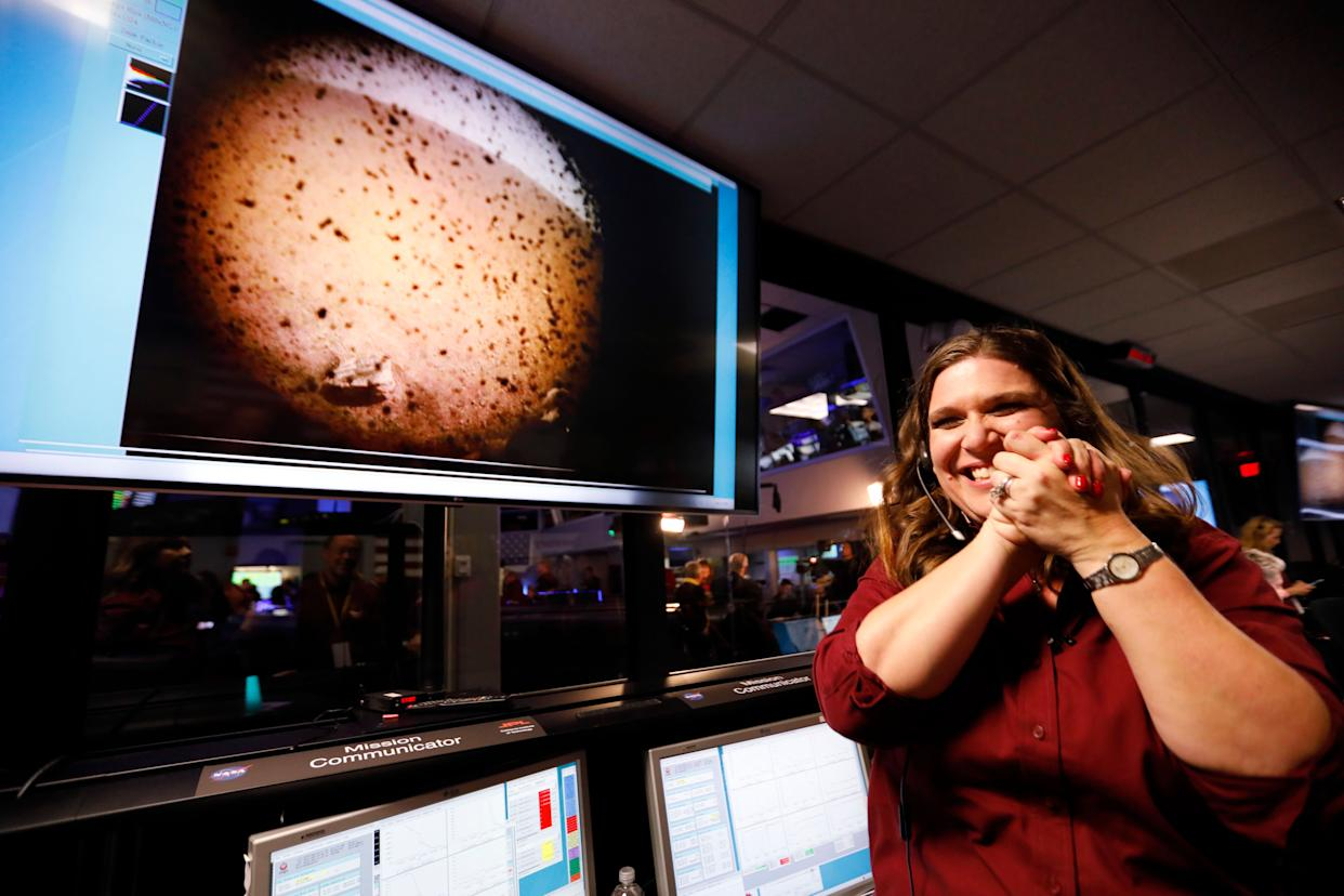 An engineer smiles next to an image of Mars sent from the InSight lander shortly after it landed on Mars. (Photo: ASSOCIATED PRESS)