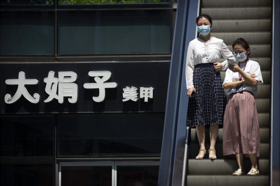 People wearing face masks to protect against the coronavirus ride an escalator past a sign of a nail salon at a shopping and office complex in Beijing, Tuesday, Aug. 11, 2020. Mainland China and semi-autonomous Hong Kong saw declines in their recent outbreaks Tuesday. (AP Photo/Mark Schiefelbein)