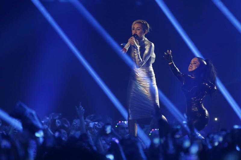 Miley Cyrus, left, and a dancer perform at the 2013 MTV Europe Music Awards in Amsterdam, Netherlands, Sunday, Nov. 10, 2013. (AP Photo/Peter Dejong)
