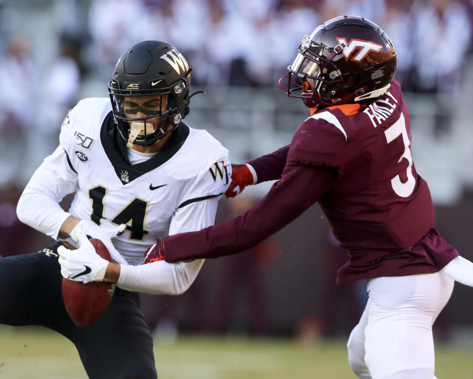 Wake Forest receiver Sage Surratt (14) catches a pass in front of Virginia Tech defender Caleb Farley (3) during the first quarter of an NCAA college football game Saturday, Nov. 9, 2019, in Blacksburg, Va. (Matt Gentry/The Roanoke Times via AP)