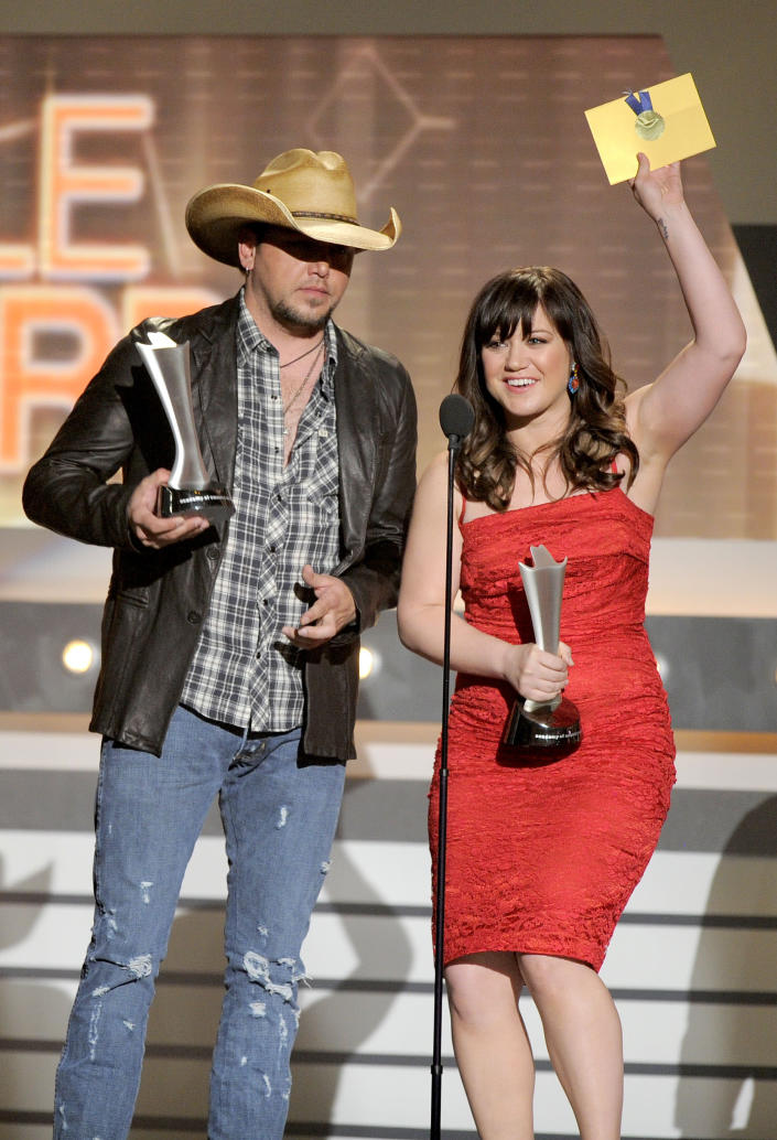 """Jason Aldean, left, and Kelly Clarkson accept the award for single of the year for """"Don't You Wanna Stay"""" at the 47th Annual Academy of Country Music Awards on Sunday, April 1, 2012 in Las Vegas. (AP Photo/Mark J. Terrill)"""