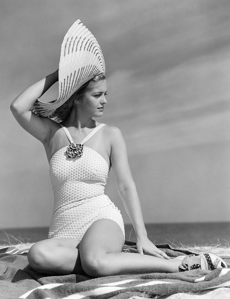 <p>A model poses on a beach in a white halter-neck bathing suit and a large straw hat. </p>