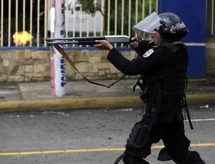 A riot police officer fires a weapon during clashes with students taking part in a protest in Managua on May 28, 2018 (AFP Photo/INTI OCON)