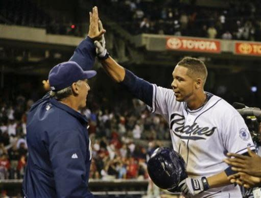 San Diego Padres' Kyle Blanks gets a high five from manager Bud Black after his game winning hit in the tenth inning gave the Padres a 4-3 victory over the Philadelphia Phillies in a baseball game in San Diego, Monday, June 24, 2013. It was Blanks' fourth hit of the game. (AP Photo/Lenny Ignelzi)