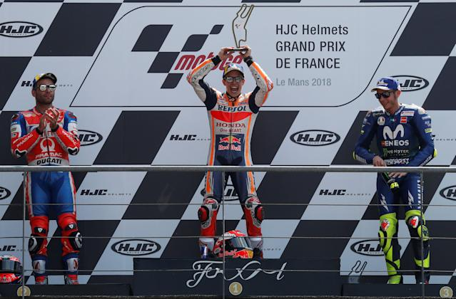 Motorcycling - MotoGP - French Grand Prix - Bugatti Circuit, Le Mans, France - May 20, 2018 Repsol Honda Team's Marc Marquez celebrates with a trophy on the podium after winning the race as Alma Pramac Racing's Danilo Petrucci and Movistar Yamaha MotoGP's Valentino Rossi look on REUTERS/Gonzalo Fuentes
