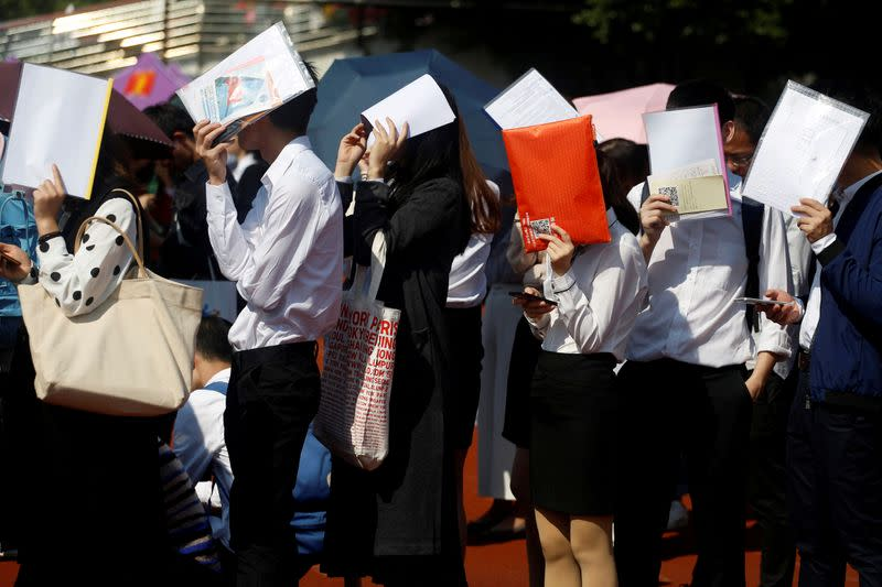 FILE PHOTO: Students shield themselves from the sun as they line up at a job fair at a university in Guangzhou