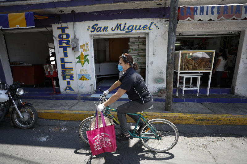Angelica Aguilar De Alba, 47, rides her bike to deliver an order of five breakfast shakes, as she tries to keep the small Herbalife business she has owned for 10 years operating, in Santa Cruz Xochitepec in the Xochimilco district of Mexico City, Wednesday, April 1, 2020. Aguilar, who has closed her indoor seating and is now offering only take out or delivery options, estimates business has fallen 50% in the last two weeks due to measures to help contain the spread of the new coronavirus. (AP Photo/Rebecca Blackwell)