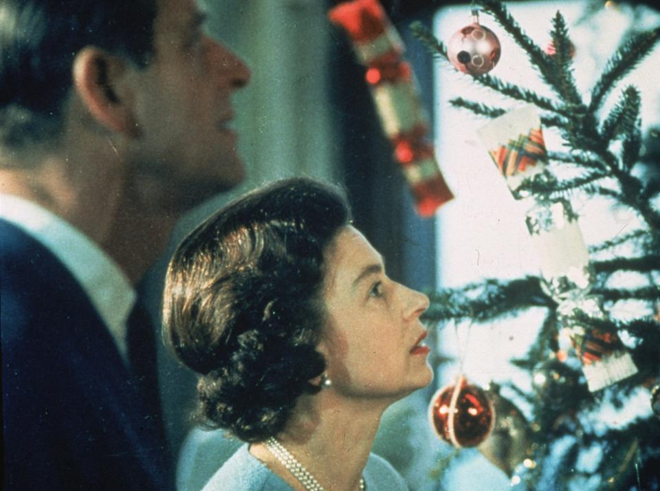 June 1969: Queen Elizabeth II and Prince Philip look at their decorated Christmas tree during the filming of a television special about life in the British royal family.    (Photo by Fox Photos/Getty Images)