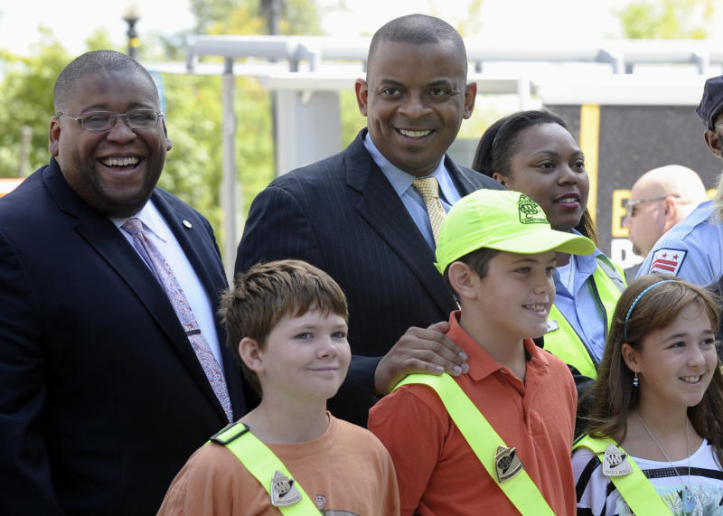 Transportation Secretary Anthony Foxx, center, and National Highway Traffic Safety Administration Administrator David Strickland, left, stand with students wearing crossing guard belts during a news conference outside the Transportation Department in Washington, Monday, Aug. 5, 2013. Secretary Foxx announced a new set of tools to help communities combat the rising number of pedestrian deaths that have occurred over the last two years. (AP Photo/Susan Walsh)