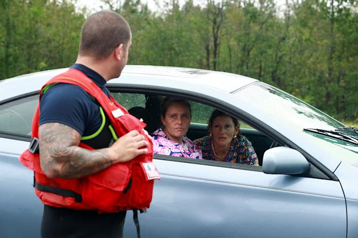 Letisha Barton asks Coast Guard Officer David Kelley about her home in the flood waters in Lumberton.