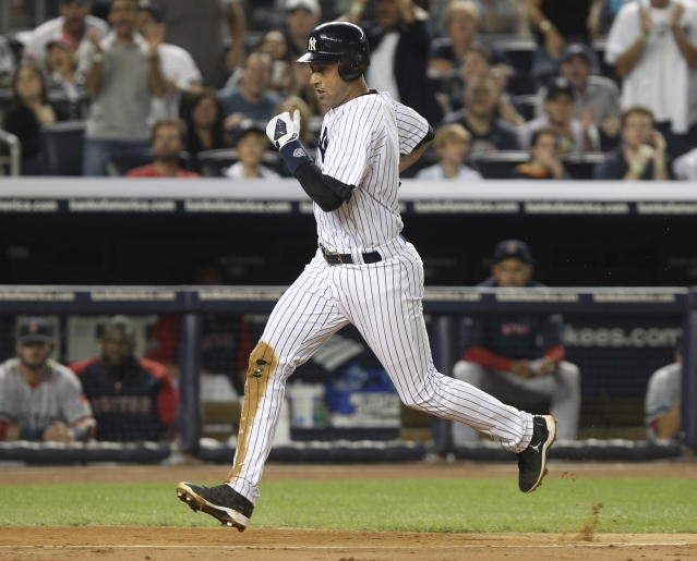 New York Yankees' Derek Jeter scores a run on a wild pitch thrown by Boston Red Sox's Josh Beckett during the third inning of the baseball game Sunday, Aug. 19, 2012 at Yankee Stadium in New York. (AP Photo/Seth Wenig)