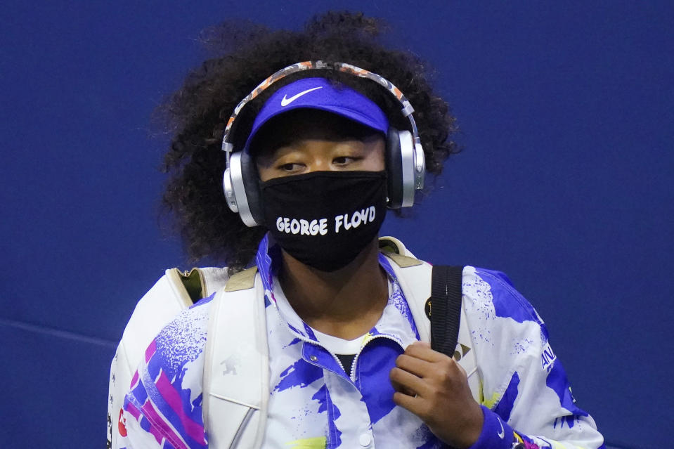 """FILE - Naomi Osaka, of Japan, wears a protective mask due to the COVID-19 virus outbreak, featuring the name """"George Floyd"""", while arriving on court to face Shelby Rogers, of the United States, during the quarterfinal round of the U.S. Open tennis championships in New York, in this Tuesday, Sept. 8, 2020, file photo. In a most unusual year already thrown into chaos by the coronavirus pandemic, many athletes took unprecedented steps when a nationwide reckoning on race spilled into the streets of American cities after the killing of Floyd, a Black man, while in Minneapolis police custody. (AP Photo/Frank Franklin II, File)"""