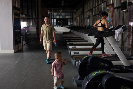 Huang Wensi's husband Deng Peipeng, looks after their son while accompanying her on a training session in a local gym in Lianjiang, Guangdong province, China, July 2, 2018. REUTERS/Yue Wu