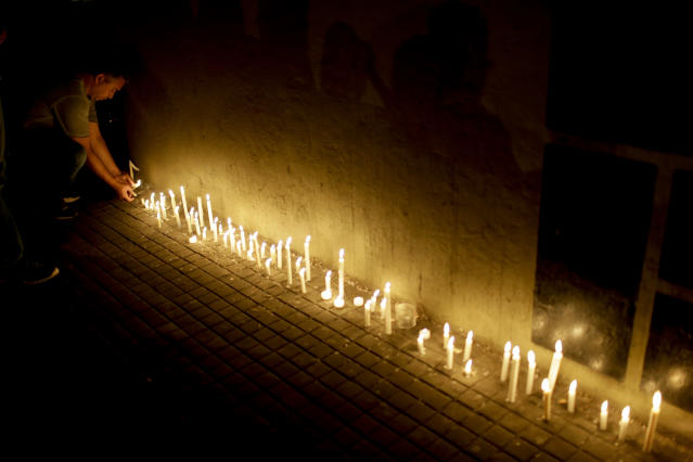 <p>A man places a candle during a vigil outside the Polytechnic School in Rosario, Argentina, Wednesday, Nov. 1, 2017. Five victims killed in the bike path attack near the World Trade Center in New York were part of a group of friends celebrating the 30th anniversary of their graduation from the Polytechnic School of Rosario, Argentina. (Photo: Natacha Pisarenko/AP) </p>