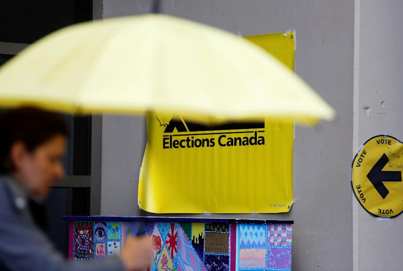 A person with an umbrella passes by the the Bonsor Recreation Complex polling station on Election Day in Burnaby, British Columbia, Canada October 21, 2019. REUTERS/Lindsey Wasson