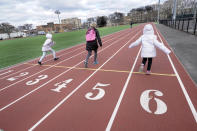 A woman and two children race on a running track, Sunday, Jan. 17, 2021, at Linden Park in the East New York neighborhood of the Brooklyn borough of New York. (AP Photo/Kathy Willens)