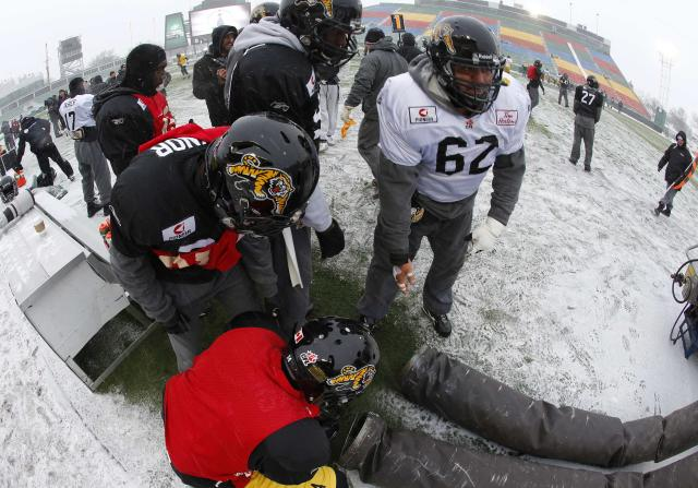 Hamilton Tiger-Cats' Marwan Hage (62) tries to keep warm with his teammates in the bitter cold during their team practice in Regina, Saskatchewan, November 20, 2013. The Saskatchewan Roughriders will play the Hamilton Tiger-Cats in the CFL's 101st Grey Cup in Regina on November 24. REUTERS/Todd Korol (CANADA - Tags: SPORT FOOTBALL)