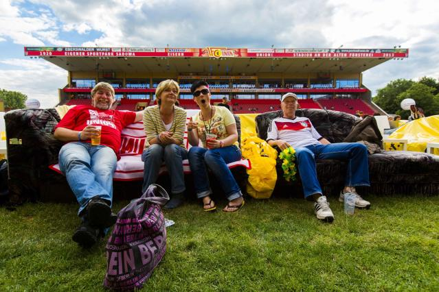 """People sit on sofas as they watch a 2014 World Cup soccer match during a public viewing event at the Alte Foersterei stadium in Berlin, June 15, 2014. Berlin's Union Berlin soccer team, which plays in the second division, has turned its stadium into a vast """"World Cup living room,"""" allowing fans to transport their own sofa onto the pitch to watch the games for free. At least 12,000 people are expected to watch Germany's first World Cup game against Portugal on Monday, on up to 850 couches. Picture taken June 15, 2014. REUTERS/Thomas Peter (GERMANY - Tags: SPORT SOCCER WORLD CUP SOCIETY)"""