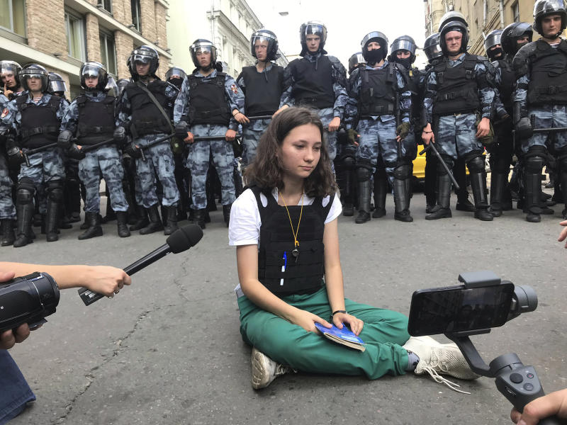 In this Saturday, July 27, 2019, photo, provided by Alexei Abanin, Olga Misik, member of the small, grassroots group Bessrochka, sits in front of police officers during an unsanctioned rally in the center of Moscow. Despite the group's small numbers, its use of new digital tools and efforts to self-organize mark a shift in civil consciousness previously unseen in Russia. (Alexei Abanin via AP)