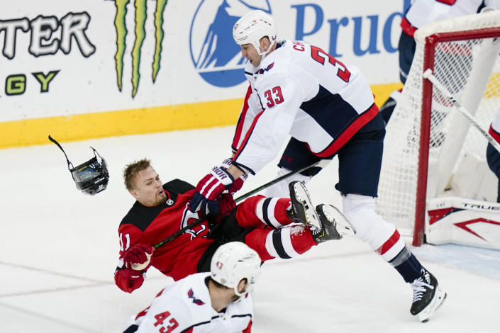 Washington Capitals' Zdeno Chara (33) checks New Jersey Devils' Andreas Johnsson (11) during the first period of an NHL hockey game Sunday, April 4, 2021, in Newark, N.J. (AP Photo/Frank Franklin II)