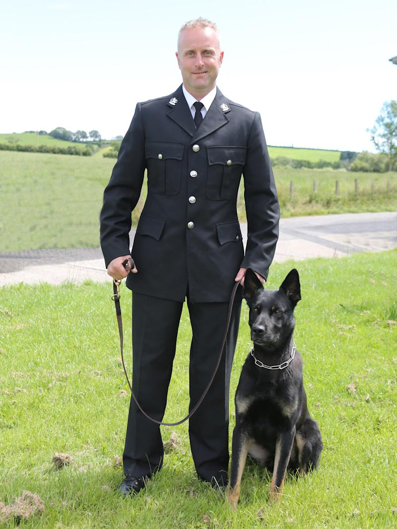 Dyfed–Powys Police Constable Peter Lloyd and police dog Max. Max found a missing woman and her child during his first shift as a police dog.