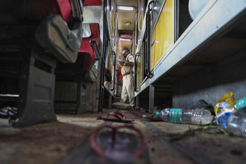 Sandals and water bottles lie scattered as a police officer inspects the interior of a parked bus onto which a truck struck overnight in Barabanki, Uttar Pradesh state, India, Wednesday, July 28, 2021. Police say a truck struck a group of laborers sleeping under the parked bus on the side of a highway in northern India, killing more than a dozen of them. (AP Photo/Sumit Kumar)