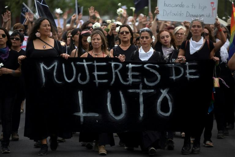 Women dressed in black march to the presidential palace in Santiago demanding justice for those killed and injured during two weeks of protests (AFP Photo/CLAUDIO REYES)
