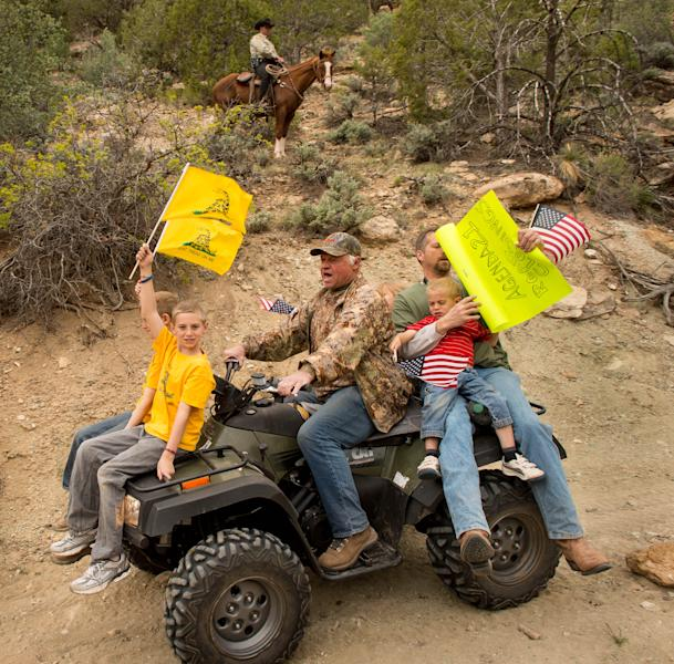 As a Kane County sheriff's deputy watches from a horse, ATV riders make their way into Recapture Canyon, north of Blanding, Utah, on Saturday, May 10, 2014, in a protest against what demonstrators call the federal government's overreaching control of public lands. The area has been closed to motorized use since 2007 when an illegal trail was found that cuts through Ancestral Puebloan ruins. The canyon is open to hikers and horseback riders. (AP Photo/The Salt Lake Tribune, Trent Nelson)