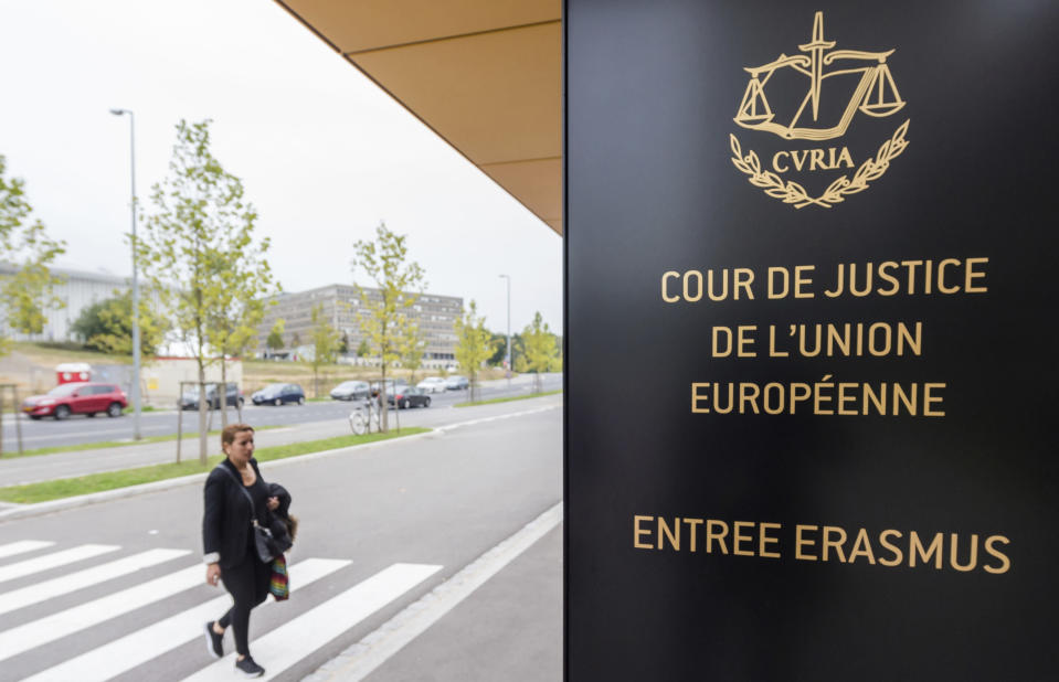 File - In this Oct. 5, 2015 file photo, a woman walks by the entrance to the European Court of Justice in Luxembourg. A European Union high court on Wednesday, July 15, 2020 ruled in favor of technology giant Apple and Ireland in its dispute with the EU over 13 billion euros, 15 billion US dollars in back taxes. (AP Photo/Geert Vanden Wijngaert, File)