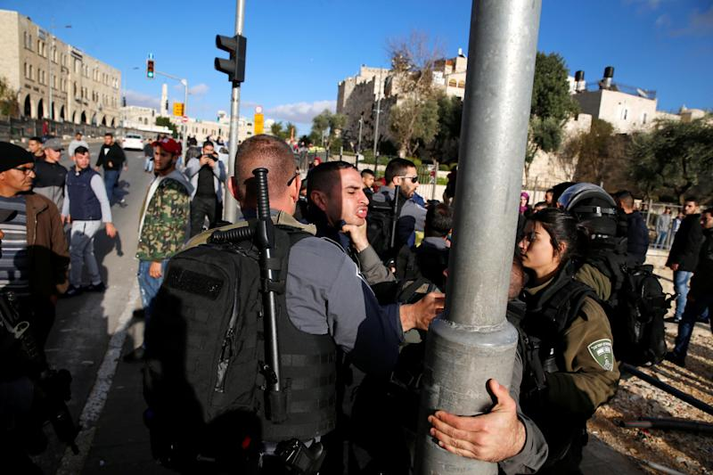 A Palestinian man scuffles with an Israeli border policeman during a protest near Damascus Gate in Jerusalem's Old City December 7, 2017.