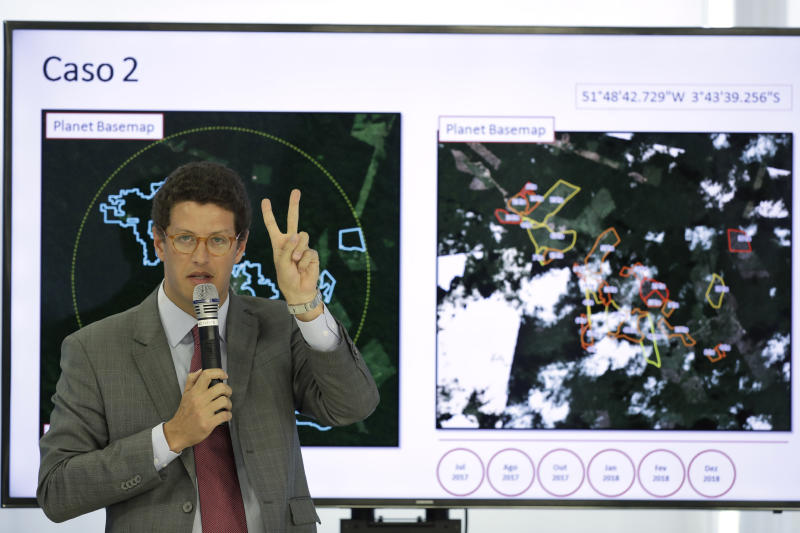Brazil's Environment Minister Ricardo Salles gives a presentation during a press conference on deforestation in the Amazon at Planalto presidential palace, where President Jair Bolsonaro is in attendance, in Brasilia, Brazil, Thursday, Aug. 1, 2019. Bolsonaro is threatening to dismiss officers at the agency that monitors deforestation in the Amazon over its publication of data he disagrees with. (AP Photo/Eraldo Peres)