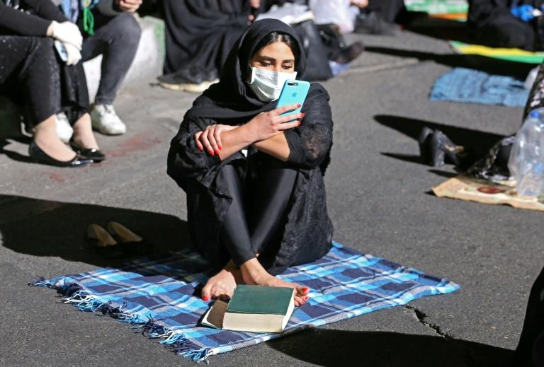 An Iranian woman wearing a face mask against the novel coronavirus prays outside a Tehran mosque during the Muslim fasting month of Ramadan (AFP Photo/ATTA KENARE)