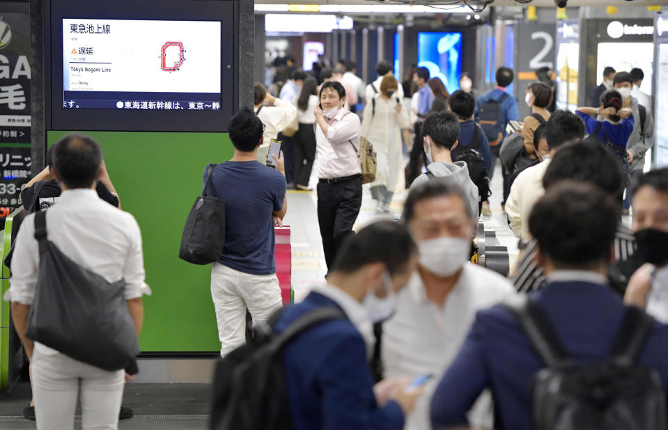 The entrance of JR Shimbashi station is crowded with passengers as the train services are suspended following an earthquake, in Tokyo, Thursday, Oct. 7, 2021. A powerful earthquake shook the Tokyo area on Thursday night, but officials said there was no danger of a tsunami.(Yoshitaka Sugawara/Kyodo News via AP)
