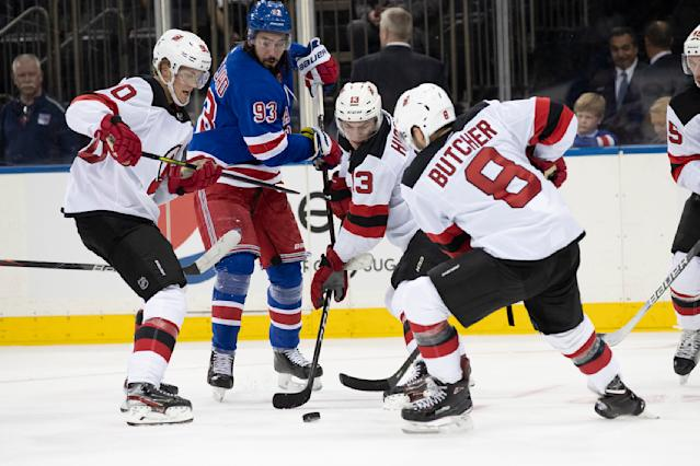 New York Rangers center Mika Zibanejad (93) fights for the puck against New Jersey Devils center Jesper Boqvist (90), defenseman Will Butcher (8) and center Nico Hischier (13) during the second period of a preseason NHL hockey game, Wednesday, Sept. 18, 2019, at Madison Square Garden in New York. (AP Photo/Mary Altaffer)