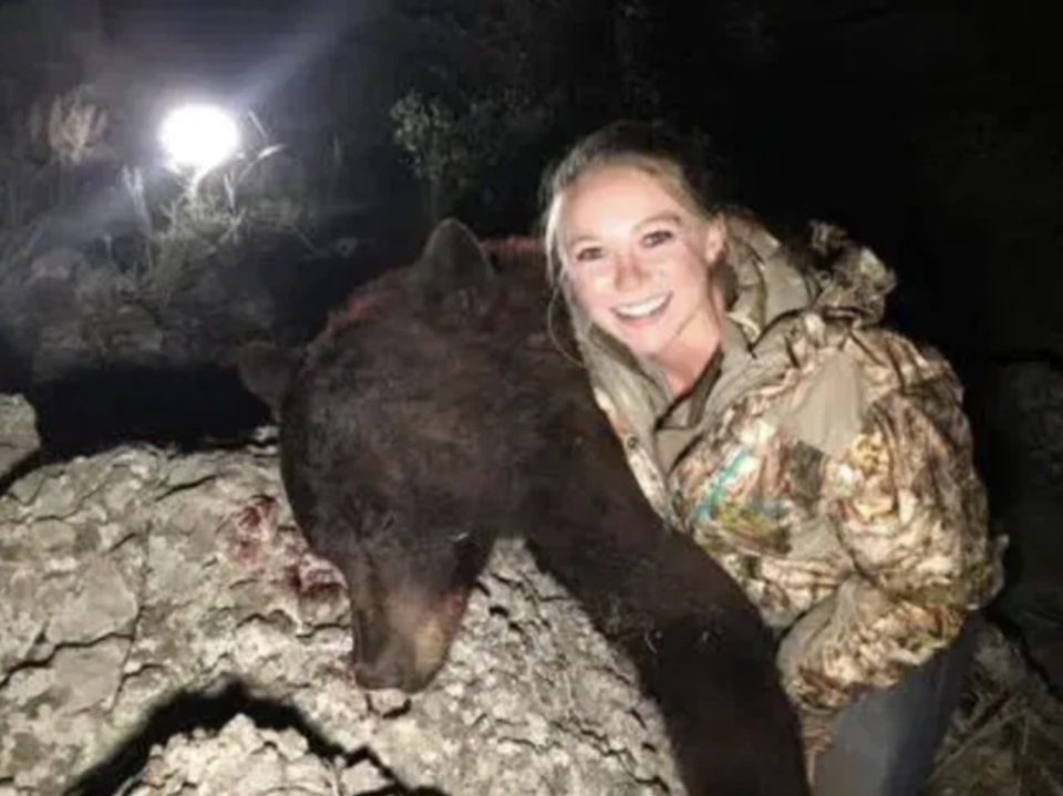 The 26-year-old posing with a dead brown bear.