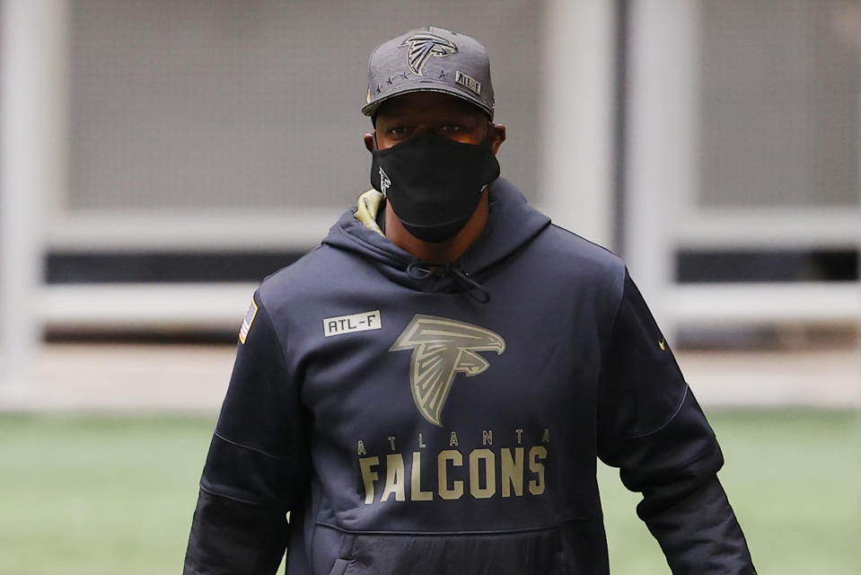 Raheem Morris, wearing a mask, looks on before a game.