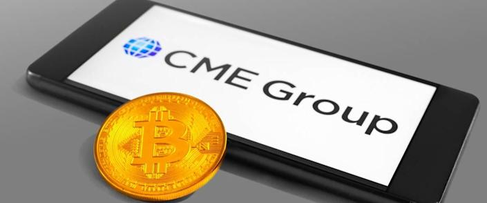 CME Group logo on a mobile device with Bitcoin coin
