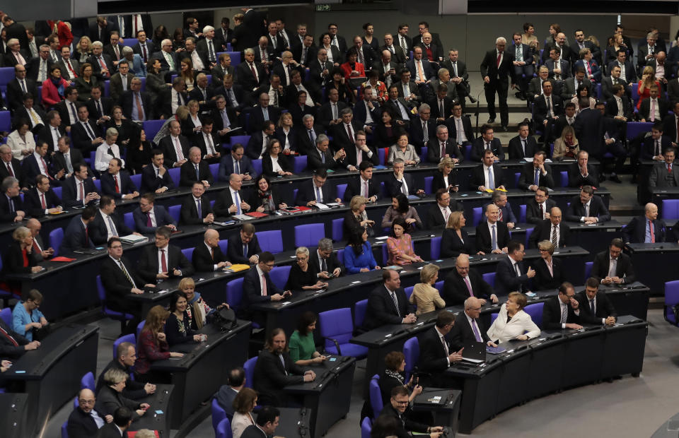 FILE - In this Wednesday, March 14, 2018 file photo, German Chancellor Angela Merkel, front row center, sits in the first row in front of the lawmakers of her center-right Christian Union block when Germany's parliament Bundestag meets to elect Angela Merkel for a fourth term as chancellor in Berlin, Germany. Before Merkel took office in 2005, 23 percent of federal lawmakers for her center-right Union bloc were women and today, the figure is 19.9 percent. (AP Photo/Markus Schreiber, File)