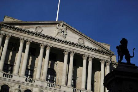 A statue is silhouetted against the Bank of England in the City of London