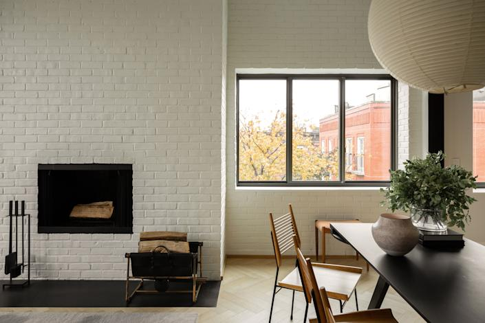 "<div class=""caption""> ""The final design of the wood-burning fireplace, an essential feature to the home, was completely unexpected,"" says Gabriela. ""Overall, the wall felt disjointed and hectic instead of a focal point. After exploring various ideas to create symmetry, we decided to embrace the original design by adding bricks to the right side wall, creating a singular surface texture along the wall. To unify the space, we <a href=""https://www.architecturaldigest.com/story/how-to-paint-brick?mbid=synd_yahoo_rss"" rel=""nofollow noopener"" target=""_blank"" data-ylk=""slk:painted the bricks white"" class=""link rapid-noclick-resp"">painted the bricks white</a>, replaced the stone hearth with blackened steel, and skipped adding a mantel. The result pays homage to the original structure of the home, while the lack of decorative elements adds a sense of modernity."" </div>"