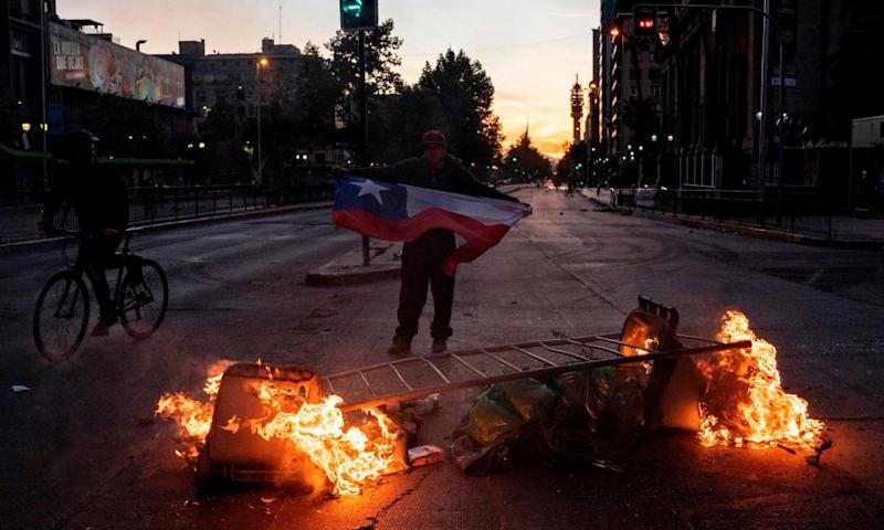 A man holds a Chilean flag in front of a barricade on Alameda Avenue in Santiago on Monday evening.